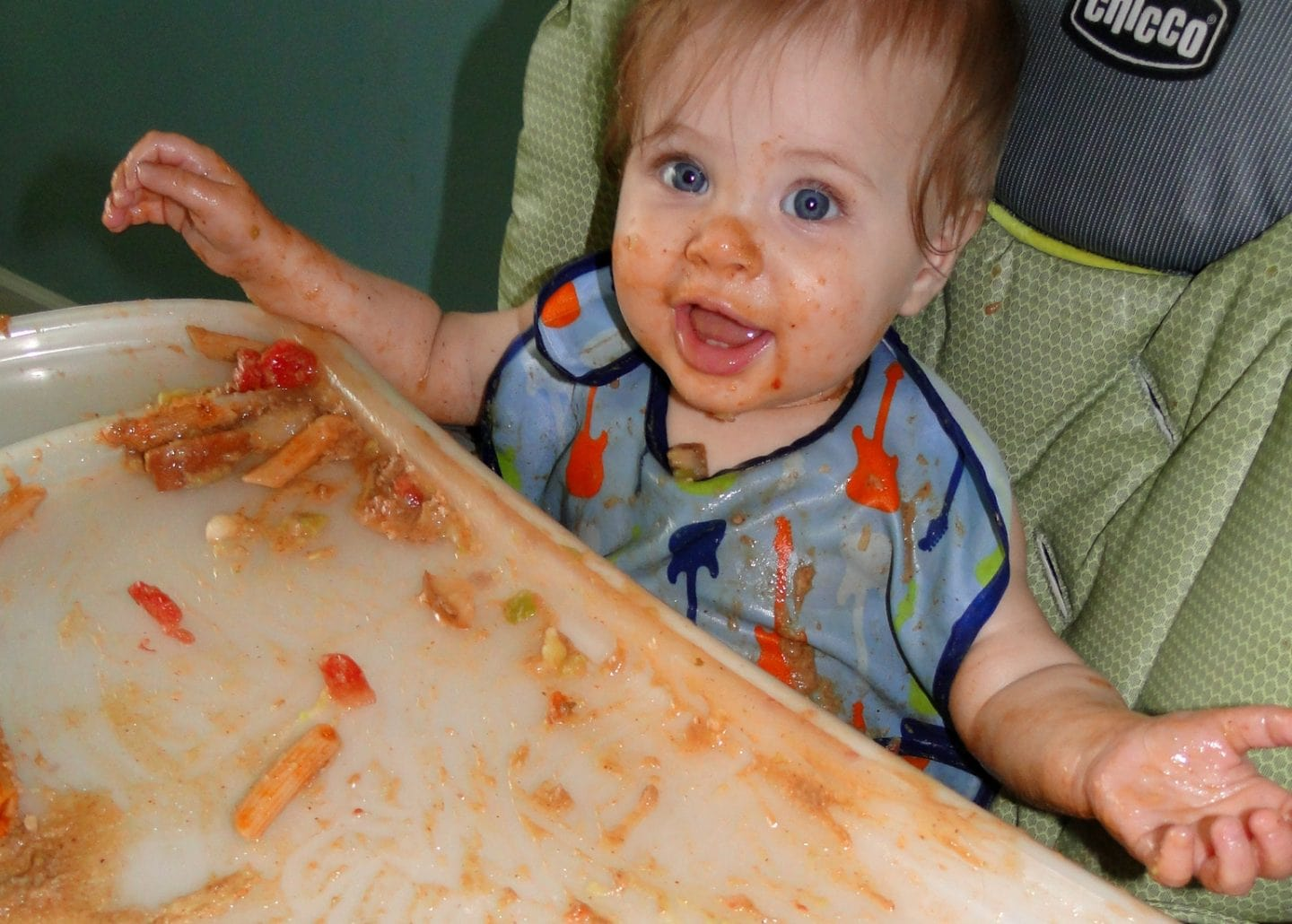 baby making mess in high chair on baby led weaning guide