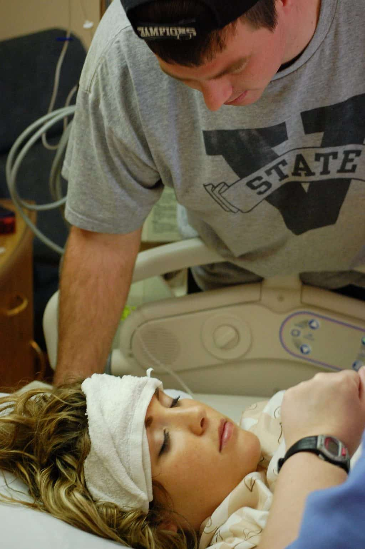 husband coaching wife through natural childbirth