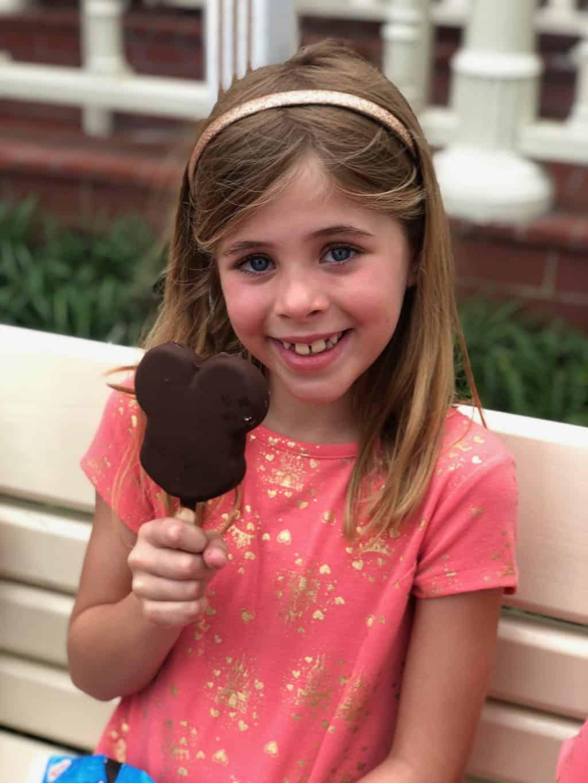girl eating mickey bar ice cream