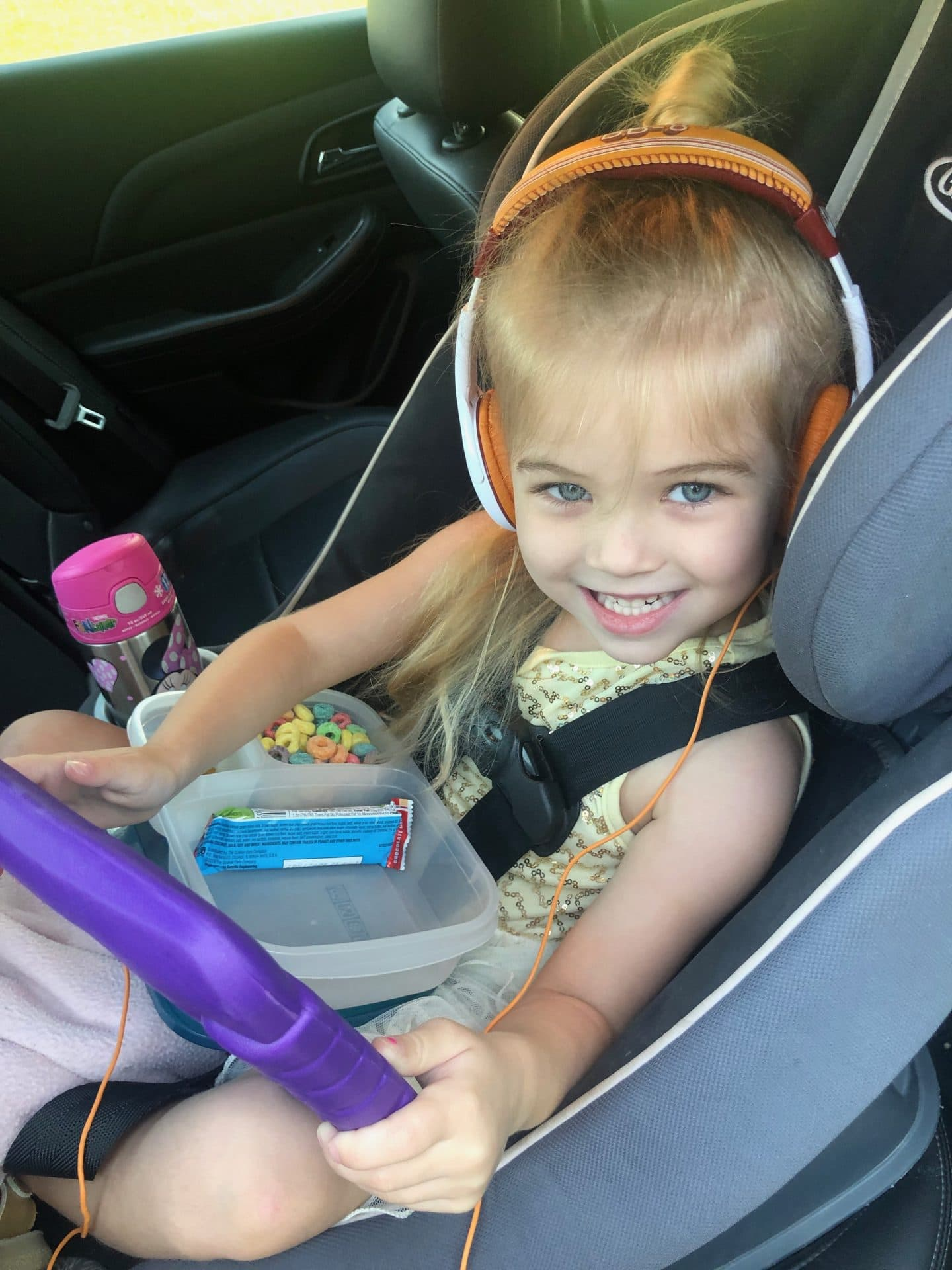 girl in car seat on road trip