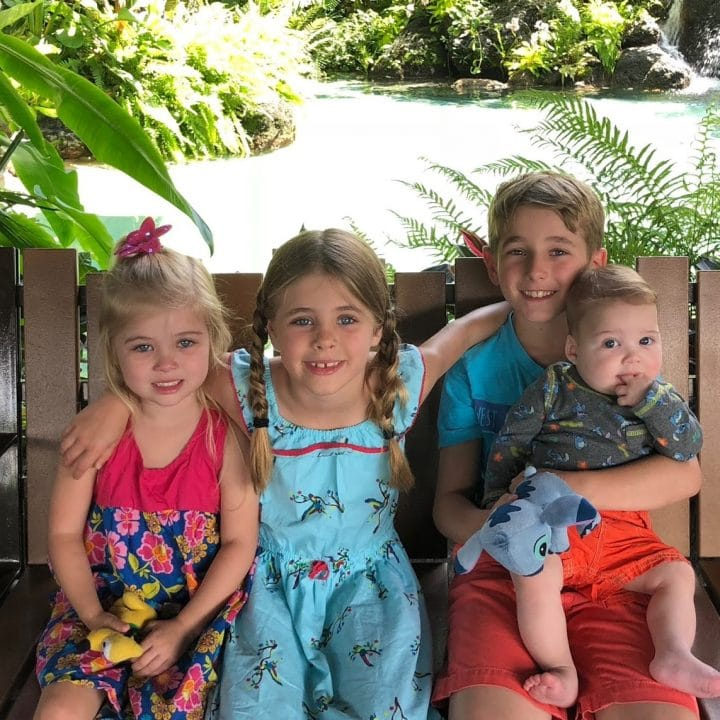 four children on a bench on vacation