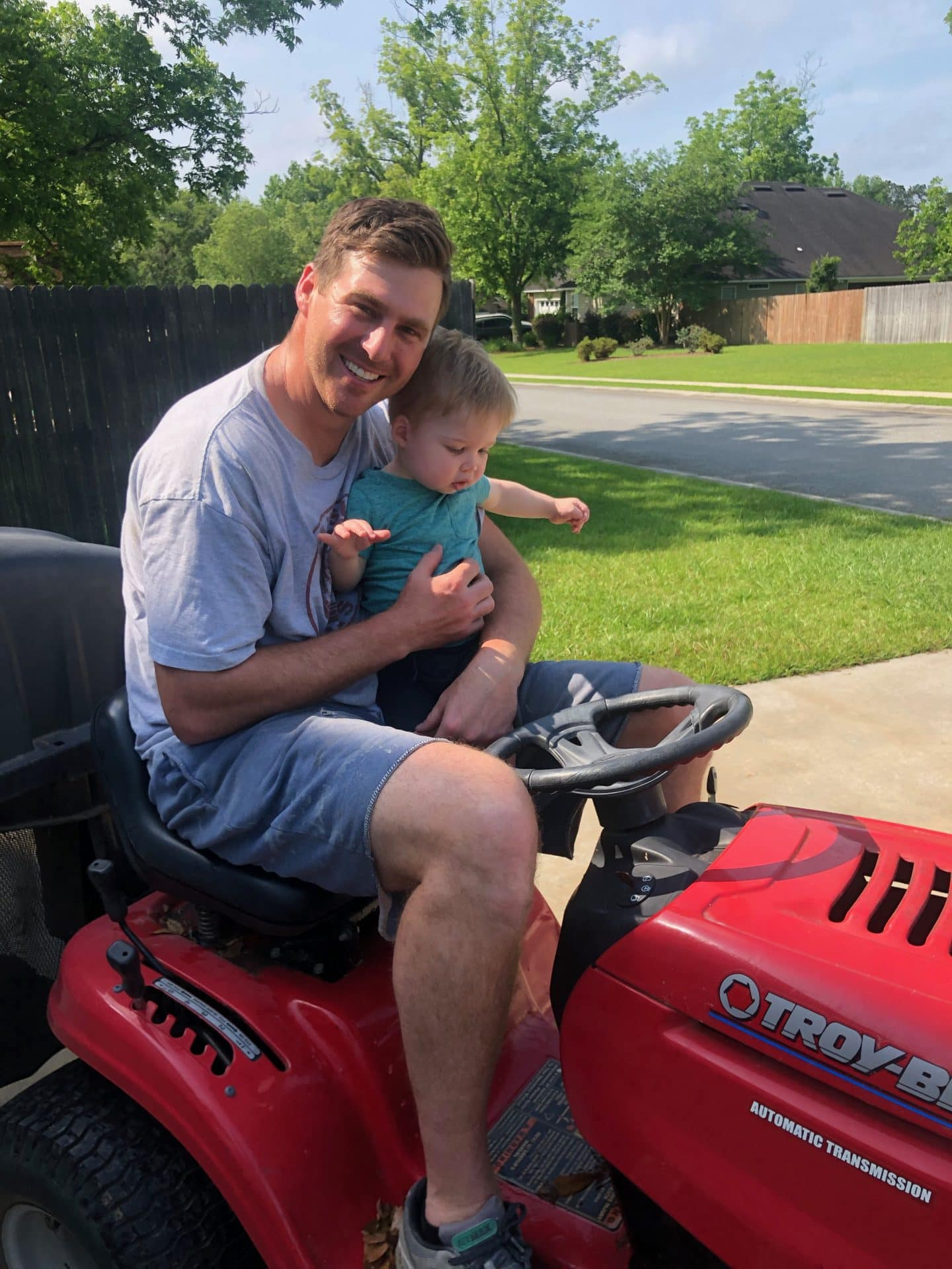 toddler helping mow grass