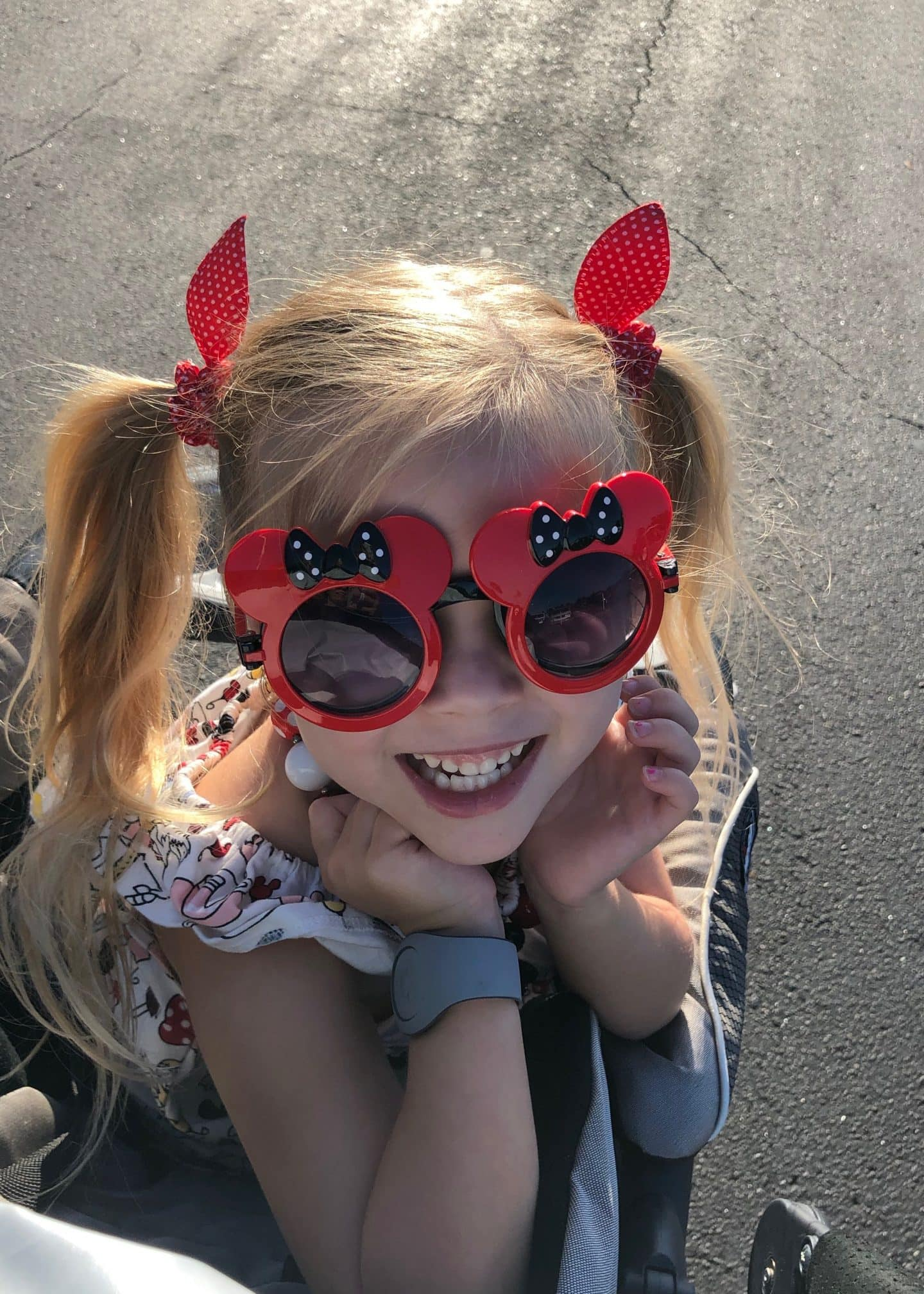 girl in magic kingdom parking lot with Minnie sunglasses