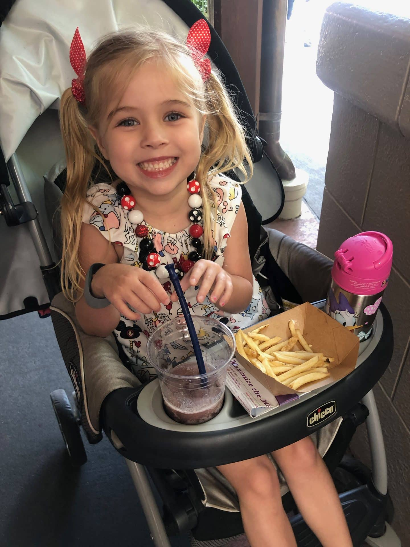 girl eating food in stroller at disney