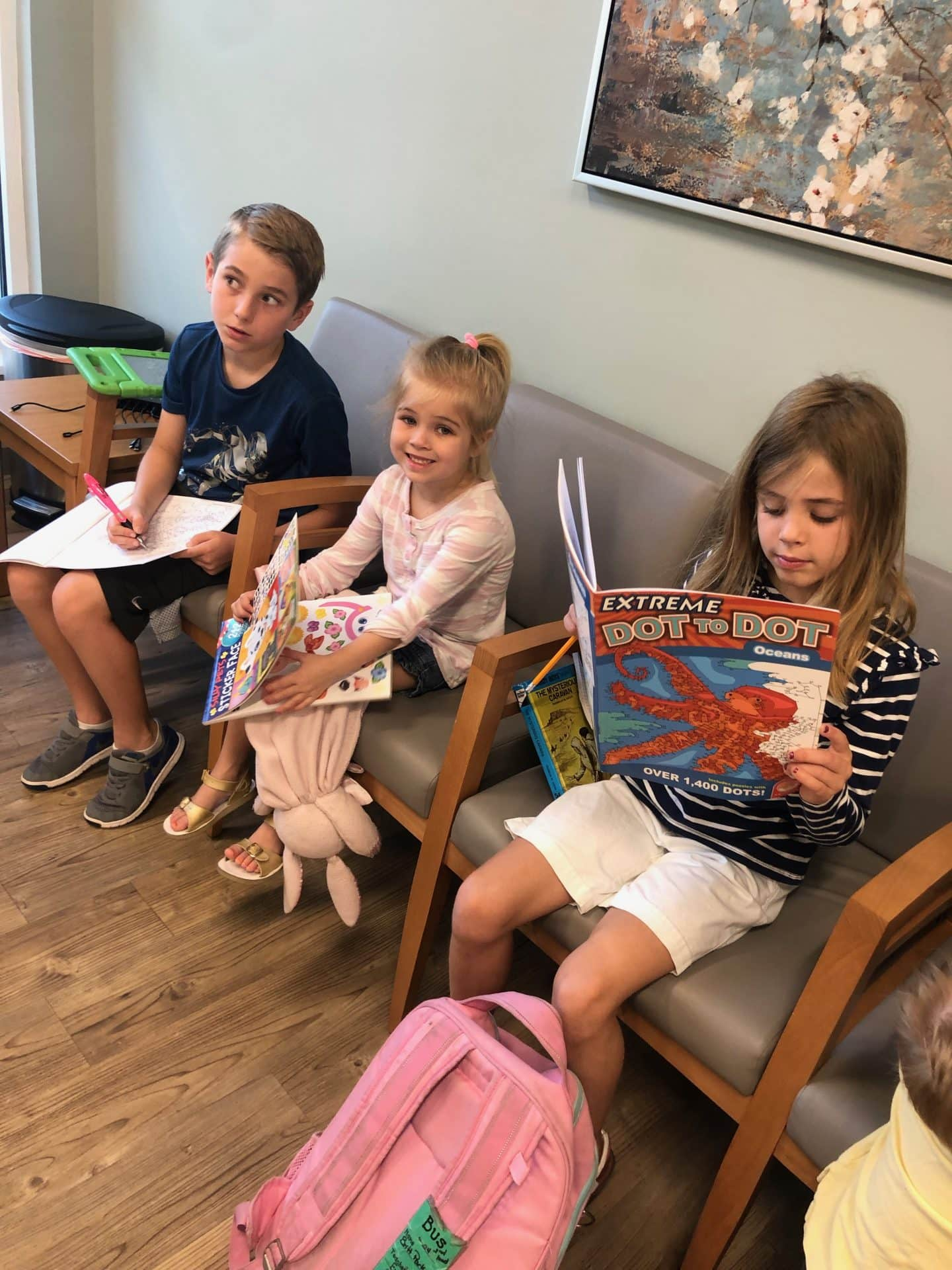 three kids sitting in dr waiting office