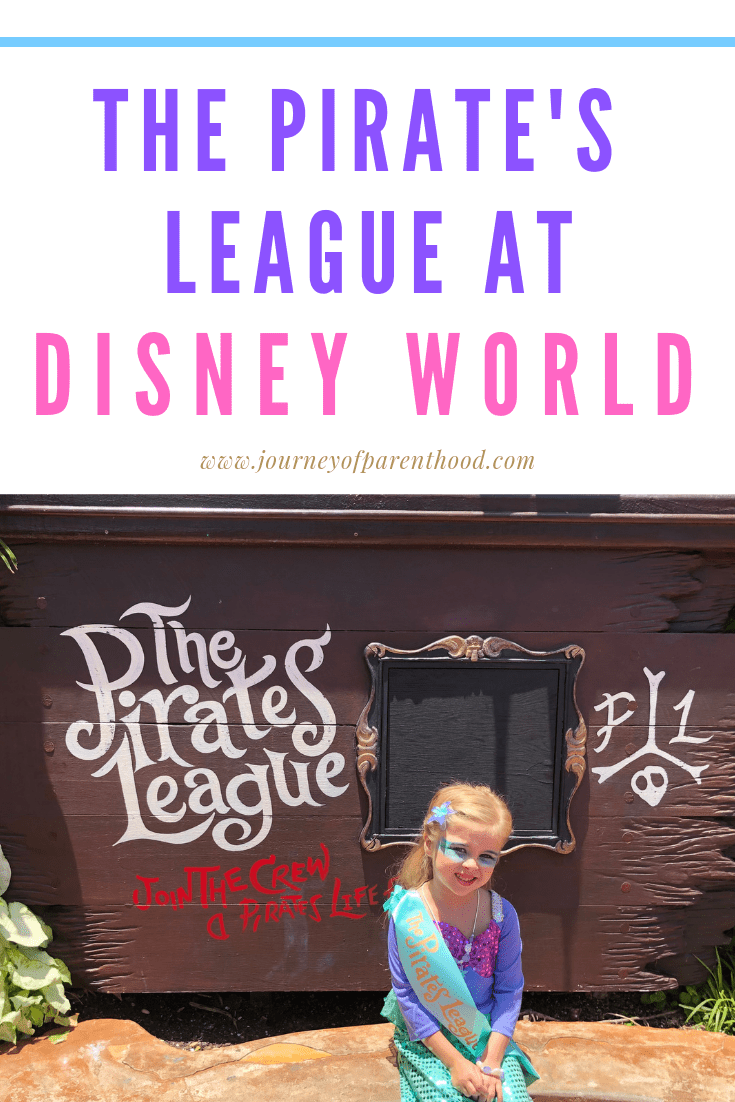 little girl makeover to a mermaid at Disney World sitting in front of the pirates league sign at magic kingdom