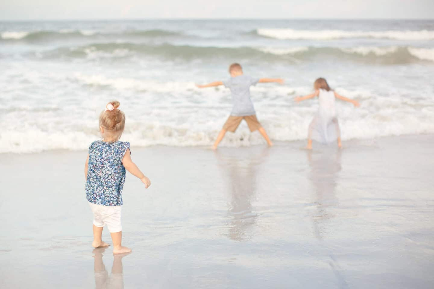 kids playing in ocean during a family photo session at the beach