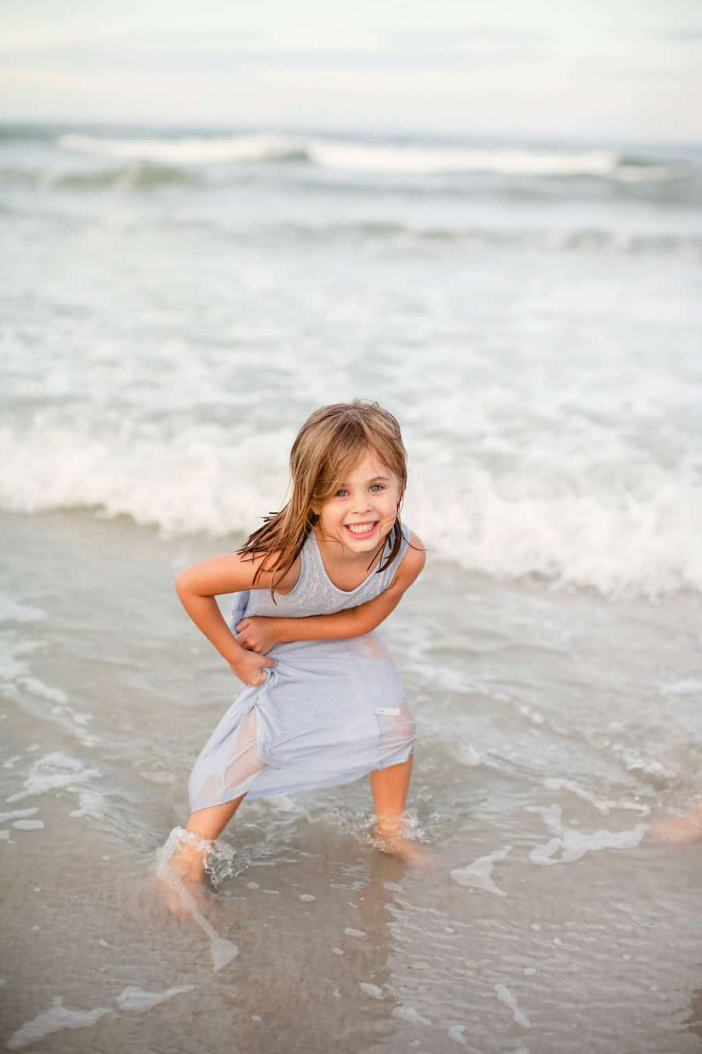 girl playing in ocean during family beach pictures