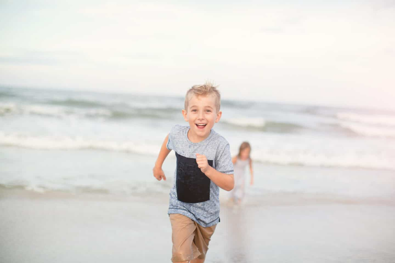 five year old boy running at the beach - candid beach photos