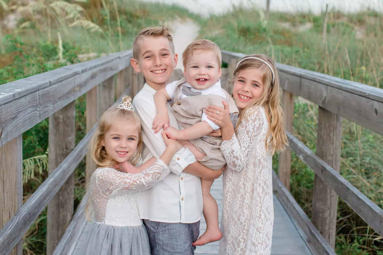 four kids at the beach taking family photos