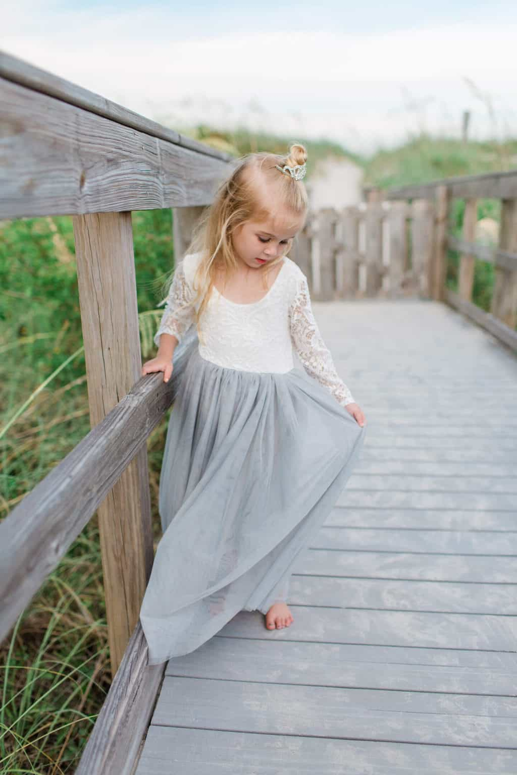 little girl holding dress on the boardwalk at the beach