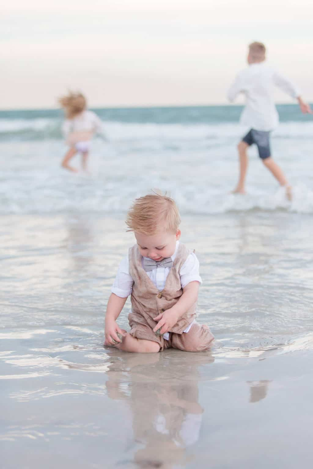 little boy playing in ocean water at the beach